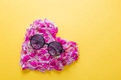 Pétales roses et pourpres de fleur dans la forme et des lunettes de soleil de coeur Photo stock