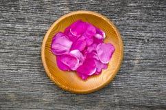 Pétalo color de rosa salvaje del escaramujo en placa de madera Imagenes de archivo