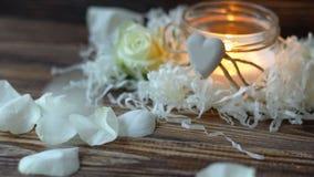 Pétalos color de rosa blancos que caen en la tabla oscura, vela ardiente en fondo almacen de video