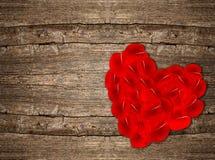 Pétalos color de rosa rojos en forma de corazón en fondo de madera Foto de archivo