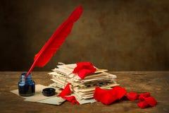 Pétalos color de rosa rojos y letras antiguas Foto de archivo libre de regalías