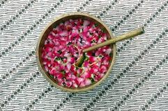 Pétalos de la flor en agua con la cucharada de oro Imagen de archivo libre de regalías