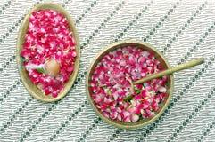 Pétalos de la flor en agua con la cucharada de oro Fotografía de archivo