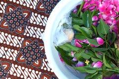 Pétalos de la flor en agua con la cucharada de oro Foto de archivo libre de regalías