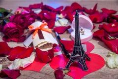 Pétalos de rosas, dinero, botellas de vino, una caja de joyas y torre Eiffel imagen de archivo