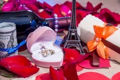 Pétalos de rosas, dinero, botellas de vino, una caja de joyas y torre Eiffel fotos de archivo libres de regalías