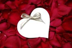 Pétalos de Rose con la etiqueta del regalo Imagenes de archivo