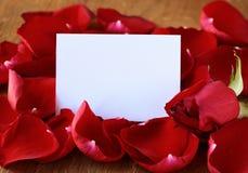Pétalos de una rosa roja y de una tarjeta Foto de archivo libre de regalías