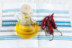 Pétrole et piments de bouteille sur le tissu fait main Images libres de droits