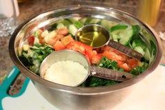 Pétrole et salade montrant des tasses de mesure avec l'huile d'olive et le parmesan comme habillage pour cette salade très coloré photo stock