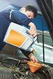 Pétrole se renversant de mécanicien de véhicule dans l'engine de moteur Images stock