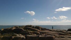 Pêchant au-dessus des roches, plage d'océan Images stock