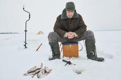 Pêche à l'hiver Morsure de attente de poissons de pêcheur Images libres de droits