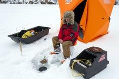 Pêche adulte de glace d'homme sur le lac jaune photo stock