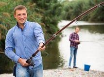 Pêche adulte enthousiaste d'homme sur le lac d'eau douce Image libre de droits