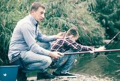 Pêche adulte enthousiaste d'homme sur le lac d'eau douce sur la forêt Image libre de droits