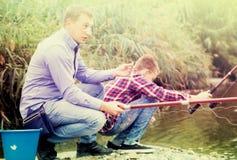 Pêche adulte enthousiaste d'homme sur le lac d'eau douce sur la forêt Images libres de droits