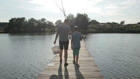 Pêche allante de père et de fils avec des tiges sur le lac