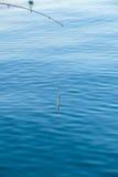 Pêche d'eau de mer - tige avec le wobbler et l'eau de mer bleue Photos stock