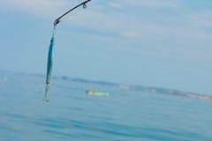 Pêche d'eau de mer - tige avec le wobbler et l'eau de mer bleue Images stock