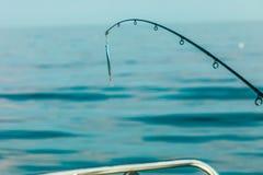 Pêche d'eau de mer - tige avec le wobbler et l'eau de mer bleue Image libre de droits
