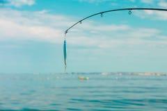 Pêche d'eau de mer - tige avec le wobbler et l'eau de mer bleue Image stock