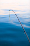 Pêche d'eau de mer - tige avec le wobbler et l'eau de mer bleue Photo libre de droits