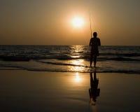 Pêche d'homme au coucher du soleil Photographie stock libre de droits