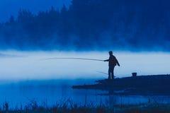 Pêche d'homme au rivage de rivière Photographie stock libre de droits