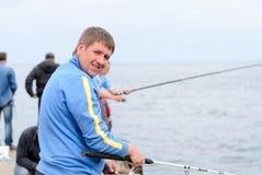 Pêche d'homme d'une jetée avec des amis Image libre de droits