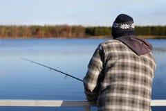 Pêche d'homme dans le Midwest sur le petit lac le jour froid photographie stock libre de droits