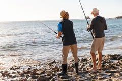 Pêche d'homme supérieur avec son petit-fils photo libre de droits