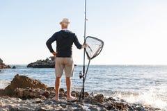 Pêche d'homme supérieur sur le côté de mer Images stock
