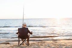 Pêche d'homme supérieur sur le côté de mer Photo stock