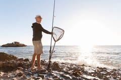 Pêche d'homme supérieur sur le côté de mer Photos libres de droits