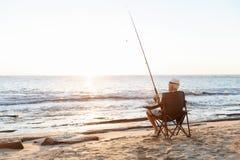 Pêche d'homme supérieur sur le côté de mer Photographie stock libre de droits