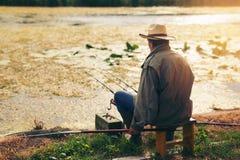 Pêche d'homme supérieur sur un lac d'eau douce se reposant patiemment Photographie stock