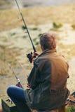 Pêche d'homme supérieur sur un lac d'eau douce se reposant patiemment Photo stock