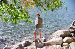 Pêche d'homme sur le lac de montagne Photos stock