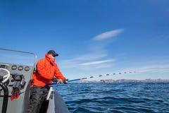 Pêche d'homme d'une canne à pêche de bateau Jupe rouge Images libres de droits