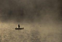 Pêche dans le brouillard de matin Images stock