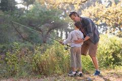 Pêche de enseignement de garçon de père dans la forêt Photos stock