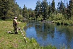 Pêche de femme avec le chapeau rose et la ligne de pêche rose Image libre de droits