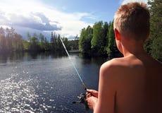 Pêche de garçon à un lac Photographie stock libre de droits