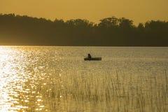 Pêche de garçon dans un kayak au coucher du soleil Photos libres de droits