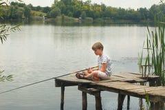 Pêche de garçon sur l'étang Photographie stock