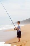 Pêche de garçon sur la plage Photo stock