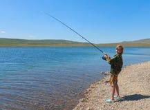 Pêche de garçon sur la rotation Image libre de droits