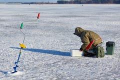 Pêche de glace d'homme sur un lac congelé image stock