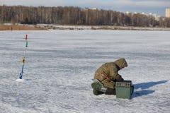 Pêche de glace d'homme sur un lac congelé images stock